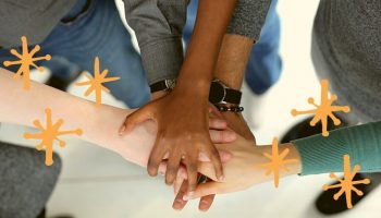 Aerial shot of a group of people standing in a circle with their hands layered on top of one another