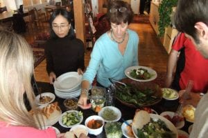Two people serve themselves at a salad bar