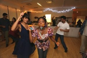 A woman blowing bubbles while others dance around her.